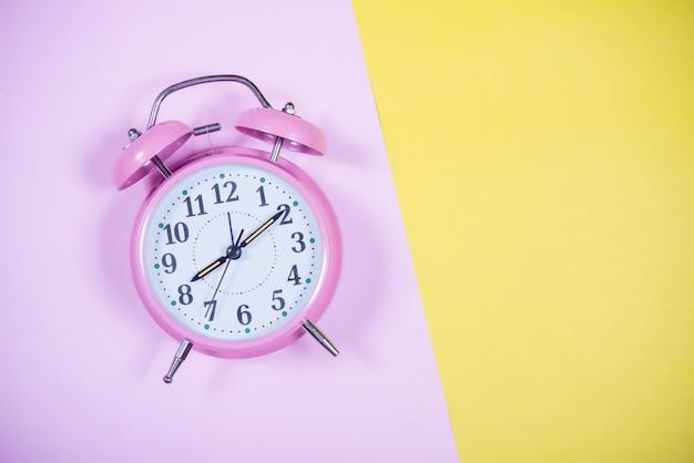 Różowy zegar na kolorowym tle, koncepcja edukacji