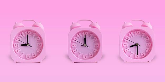 Różowy zegar odizolowywający na pastelowym różowym tle. 09:00, 08:30, 12:00. budzik