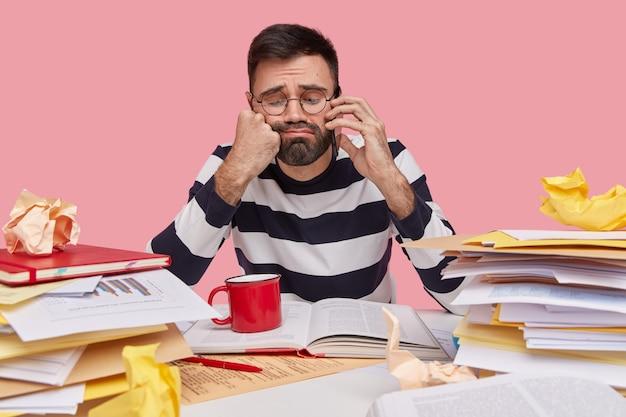 Rozpaczliwy mężczyzna ma niezadowolony wyraz twarzy, czuje się smutny i samotny, rozmawia przez telefon komórkowy, trzyma pięść pod brodą, nosi ubrania w paski