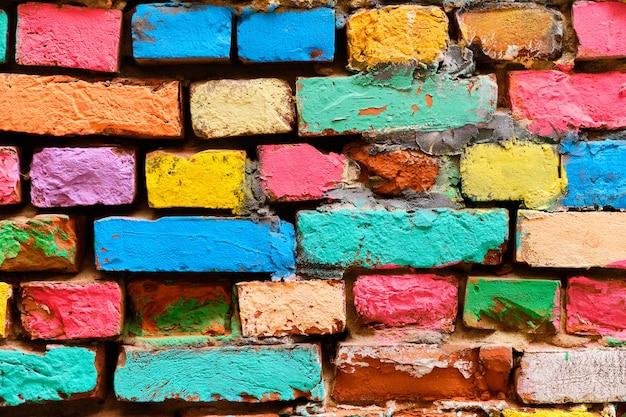 Rozpadający się ceglany mur w różnych kolorach malowanych.