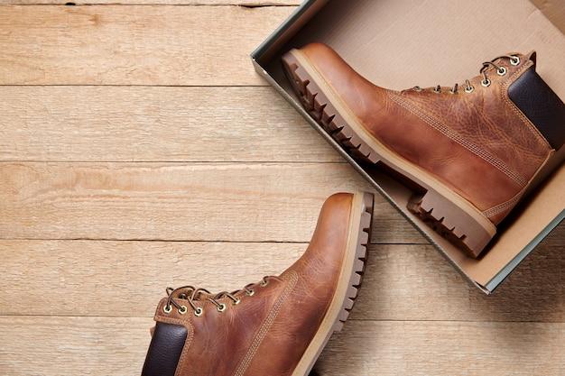 Rozpakowanie męskich skórzanych brązowych wodoodpornych butów na zimowe lub jesienne wędrówki w pudełku.