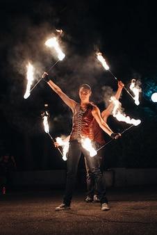 Rozpal nocny pokaz ognia z udziałem ludzi, światła i otwartego ognia