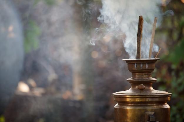 Rozpalając stary brązowy samowar, kładąc drewno opałowe do podgrzania wody do parzenia herbaty, selektywna ostrość