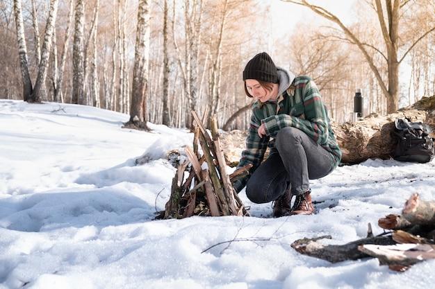 Rozpalanie ogniska w śnieżnym lesie brzozowym.