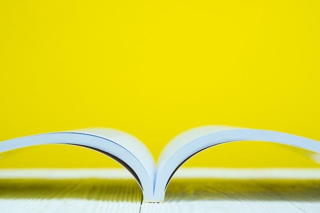 Rozpieczętowana książka na bielu stole z żółtą sceną.