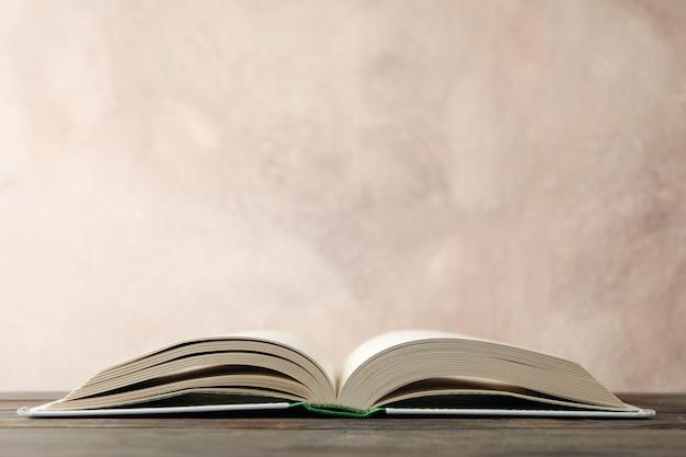 Rozpieczętowana książka na drewnianym stole przeciw brąz przestrzeni, przestrzeń dla teksta