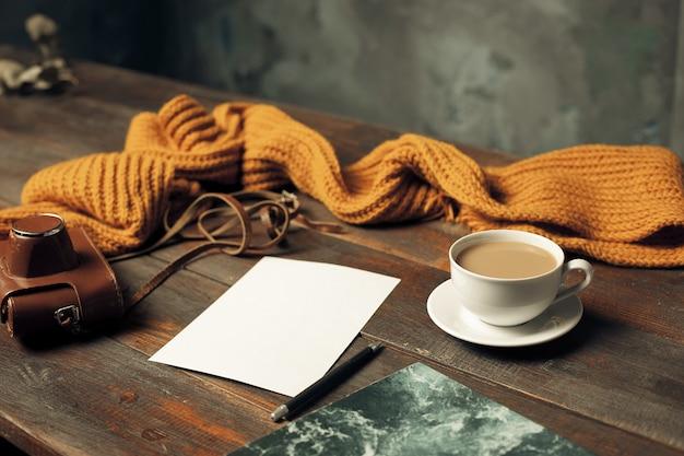 Rozpieczętowana papierowa koperta, jesień liście i kawa na drewnianym stole