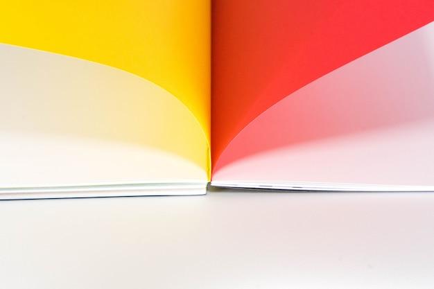 Rozpieczętowana puste miejsce książka przy białym czerwonym żółtym żółtym projekta papieru tłem.