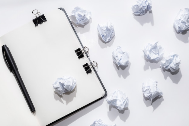Rozpieczętowany notatnik na białym tle z zmiętymi papierami