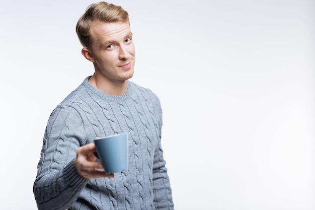 Rozpieść siebie. przystojny młody mężczyzna w szarym swetrze trzyma niebieską filiżankę kawy, stojąc na szarym tle