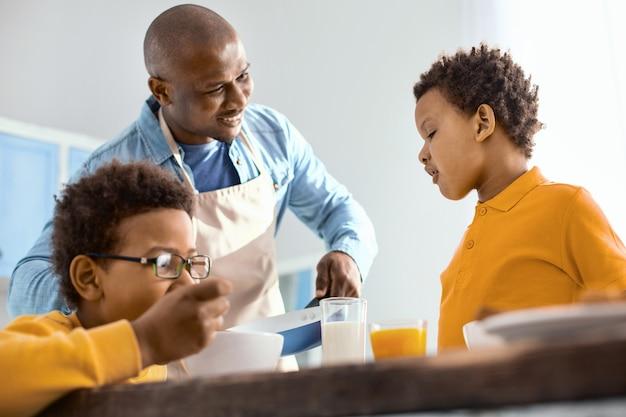 Rozpieść siebie. szczęśliwy młody ojciec trzyma patelnię i oferuje synowi omlet podczas ich śniadania