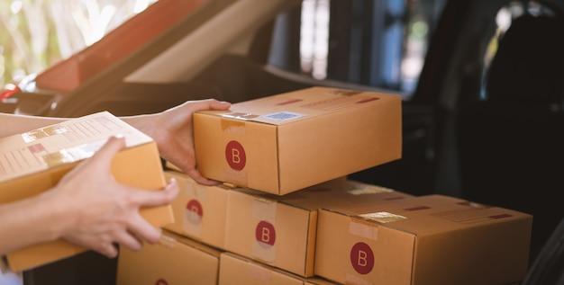 Rozpoczęcie małej firmy, ręczne pakowanie pudełek na produkty do wysłania do klientów, praca w domowym biurze