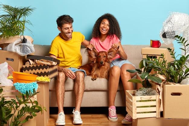 Rozpoczęcie nowego życia w nowo zakupionym mieszkaniu. szczęśliwa różnorodna kobieta i mężczyzna bawią się z psem, bawią się jego uszami, pozują na kanapie, muszą wszystko uporządkować, cieszyć się pierwszym dniem w nowym domu