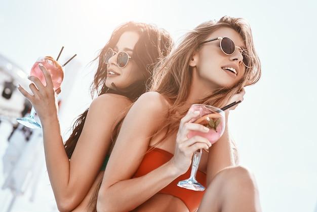 Rozpoczęła się letnia zabawa dziewczyn siedzących przy basenie i pijących koktajle