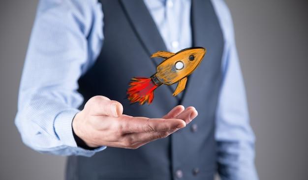 Rozpocznij koncepcję z biznesmenem posiadającym cyfrową rakietę