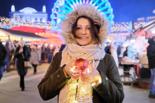 Rozpocznij nowy rok 2021, szczęśliwa kobieta pokazująca czerwoną bombkę z tekstem 2021 na jarmarku bożonarodzeniowym