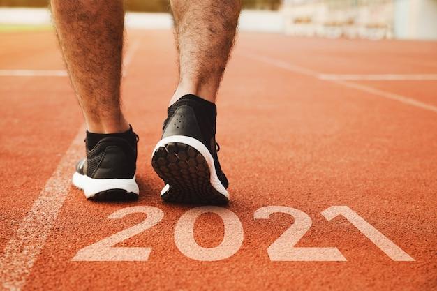 Rozpocznij z bliska na bucie sportowca biegacza biegnącego do sukcesu i nowych osiągnięć na ścieżce z koncepcją zdrowia napisem
