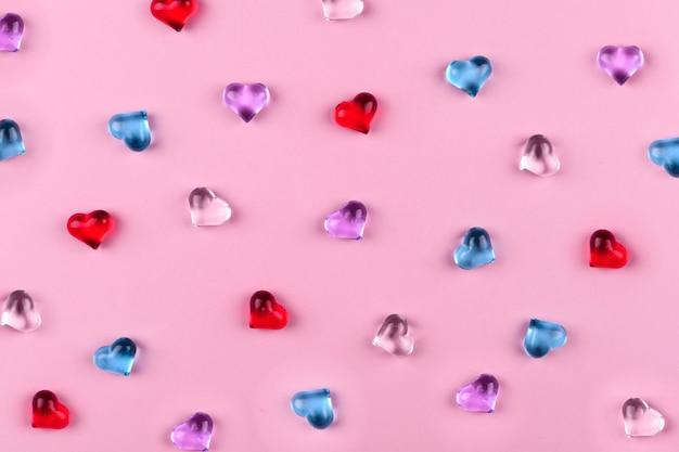 Rozpraszanie kolorowych serc ze szkła na różowym tle na walentynki.