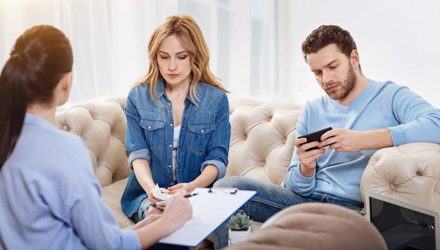 Rozpraszanie się. poważny, spokojny, przystojny mężczyzna siedzący w gabinecie psychologa i trzymając smartfon podczas gry na nim