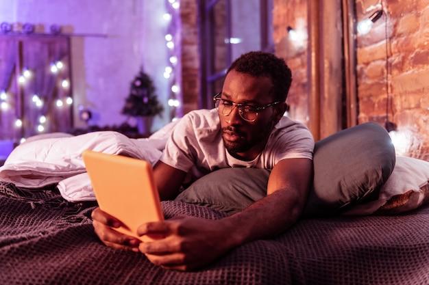 Rozpromieniony afroamerykanin. uważny przystojny facet w przezroczystych okularach leży w łóżku i sprawdza zawartość na tablecie