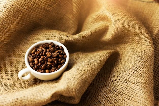 Rozproszenie ziaren kawy przy filiżance kawy.