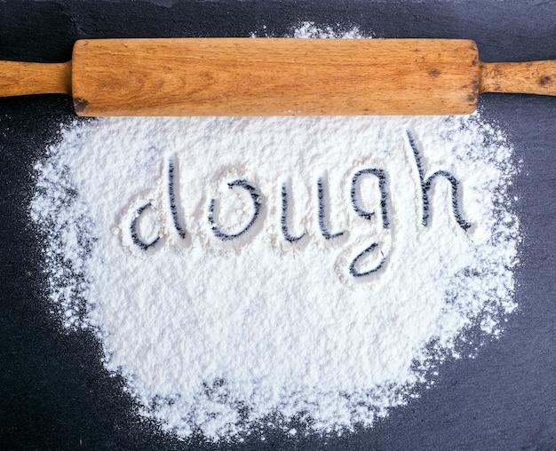 Rozproszona biała mąka pszenna i drewniany wałek do ciasta
