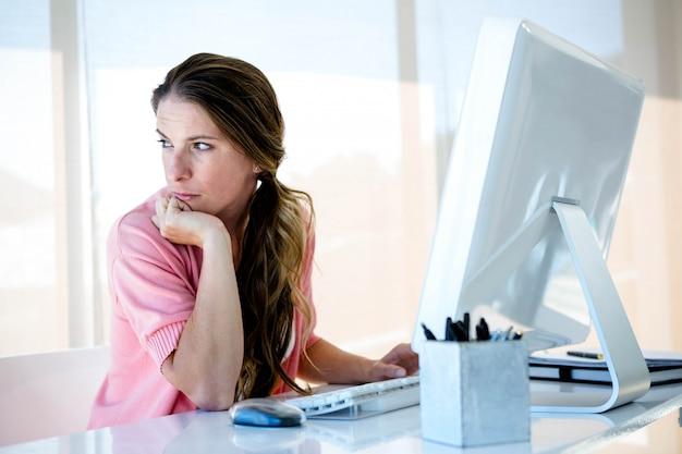 Rozproszona kobieta biznesu siedzi przy biurku, odwracając wzrok od swojego komputera