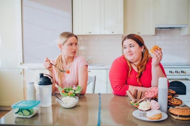Rozproszona młoda, dobrze zbudowana kobieta je ser i patrzy na modelkę w dużych rozmiarach, która trzyma burgera w dłoni. szczęśliwe ciało pozytywne. zdrowe i niezdrowe zachowanie.