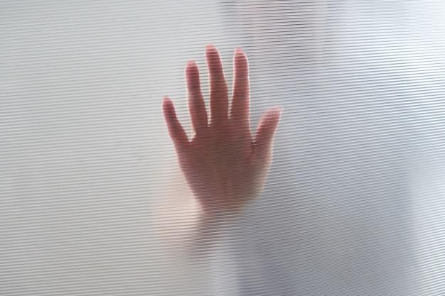 Rozproszona sylwetka kobiecych rąk przez plastik