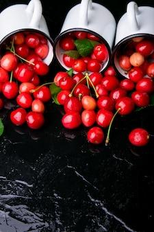 Rozproszona wiśnia z emaliowanych miseczek. czereśnie w żelaznej filiżance na czerni. zdrowe, letnie owoce. wiśnie. trzy. ścieśniać.