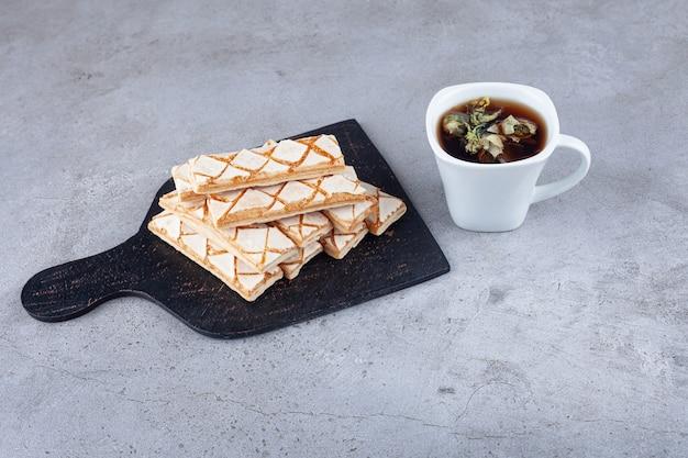 Rozproszone ciasteczka waflowe z filiżanką herbaty ziołowej.