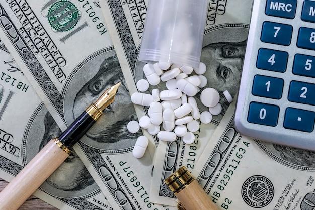 Rozproszone tabletki na banknotach dolarowych z piórem i kalkulatorem