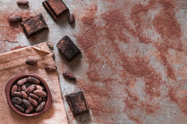 Rozproszony proszek kakaowy z kawałkami czekolady i miską ziaren kakaowych
