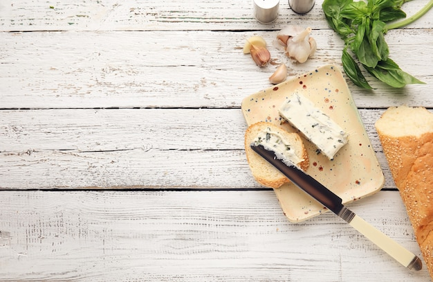 Rozprowadzanie masła czosnkowego na kromkę chleba na jasnym tle drewnianych