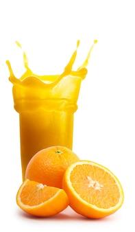 Rozpryskaj szklankę soku pomarańczowego z ciętymi pomarańczami