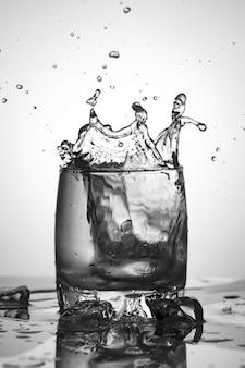 Rozpryski wody. szklanka wody z lodem.