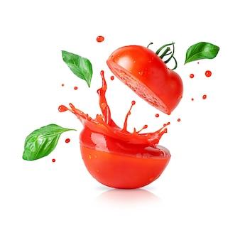 Rozpryskiwania soku pomidorowego z latającymi liśćmi bazylii na białym tle.