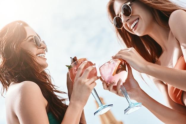 Rozpryskiwanie się w słońcu z bliska dziewcząt siedzących przy basenie, które bawią się?