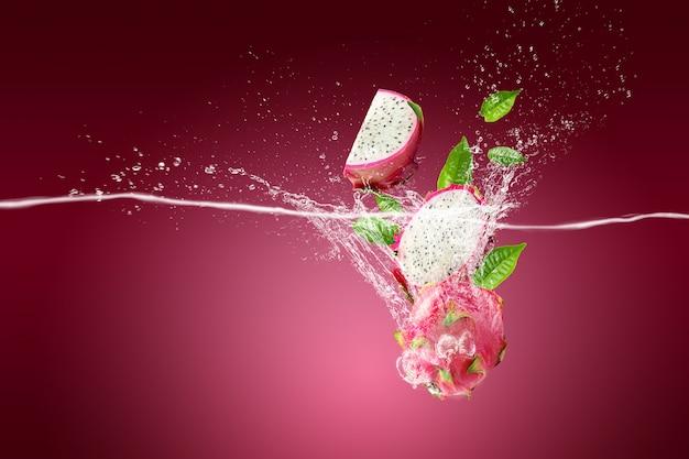 Rozpryskiwanie wody na owoc smoka lub pitaya na różowym tle
