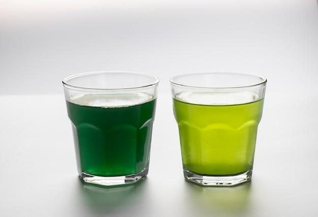 Rozpuszczona spirulina w proszku i chlorella w przezroczystych szklanych kubkach na białym tle.
