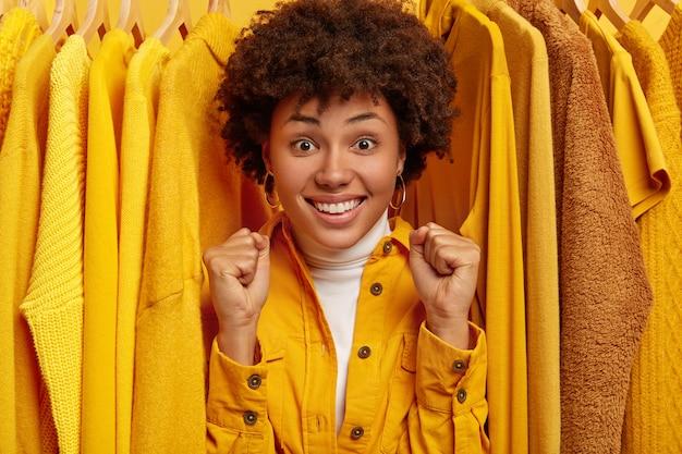 Rozradowana ciemnoskóra kobieta zaciska pięści, cieszy się z odnowienia garderoby, stoi między żółtymi strojami na wieszakach, stoi w przymierzalni. koncepcja ludzi i mody