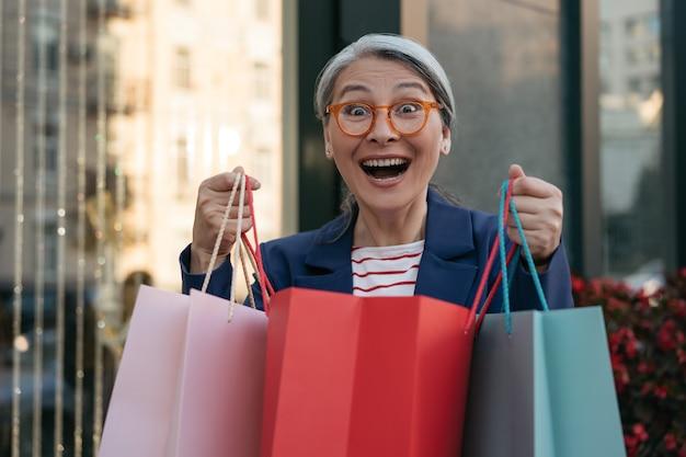 Rozradowana dojrzała azjatycka kobieta trzymająca torby na zakupy w pobliżu centrum handlowego koncepcja sprzedaży w czarny piątek