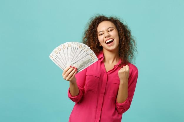 Rozradowana dziewczyna afryki robi gest zwycięzcy trzymać wentylator pieniędzy w banknotach dolara, pieniądze w gotówce na białym tle na tle niebieskiej ściany turkus. koncepcja życia szczere emocje ludzi. makieta miejsca na kopię.
