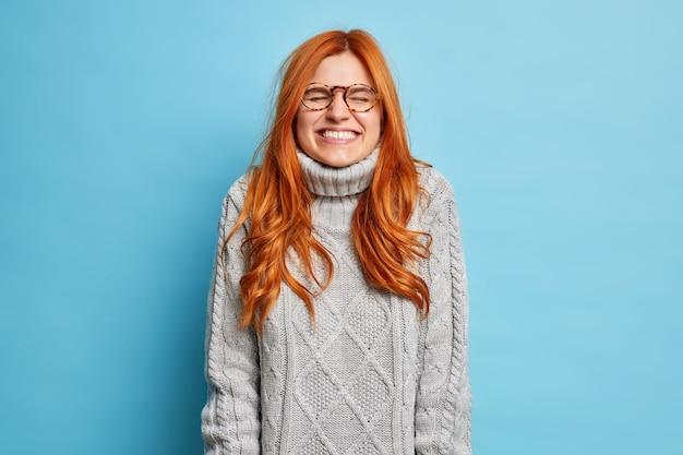 Rozradowana emocjonalnie kobieta z naturalnymi rudymi włosami, szeroko uśmiechnięta, nie może przestać się śmiać, uśmiecha się z radości, zamyka oczy ubrana w dzianinowy sweter.