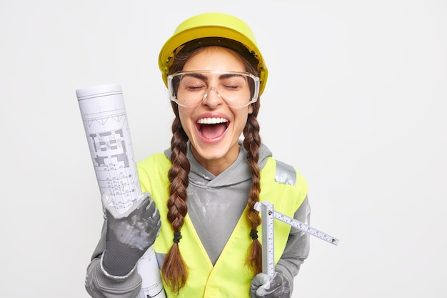Rozradowana kobieta inżynier śmieje się szczęśliwie z zamkniętymi oczami, dobrze się bawi, trzyma projekt architektoniczny, a taśma miernicza raduje się, aby osiągnąć wspaniałe wyniki, ubrana w roboczy mundur na białej ścianie