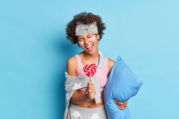 Rozradowana kobieta ubrana w bieliznę nocną trzyma poduszkę i słodkie cukierki śpiewa ulubioną piosenkę, którą wygłupia przed pójściem spać odizolowana na niebieskiej ścianie