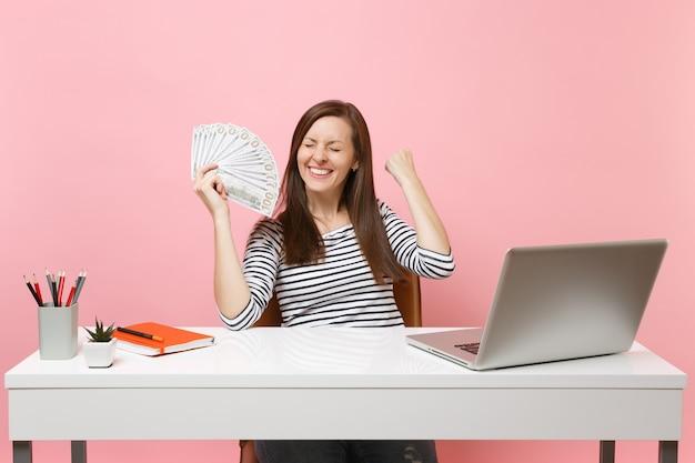 Rozradowana kobieta zaciskająca pięści jak zwycięzca trzymająca pakiet wielu dolarów, gotówka pracuje w biurze przy białym biurku z laptopem pc
