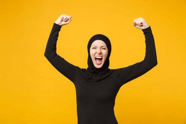 Rozradowana młoda arabska muzułmańska kobieta w hidżabowych czarnych ubraniach robi gest zwycięzcy, powiedz tak na białym tle na żółtej ścianie, portret. koncepcja życia religijnego ludzi.