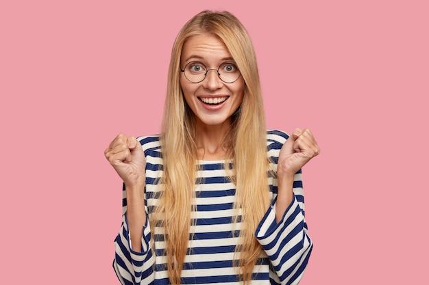 Rozradowana młoda europejka z szerokim uśmiechem, zaciska zęby, pozytywnie patrzy na aparat