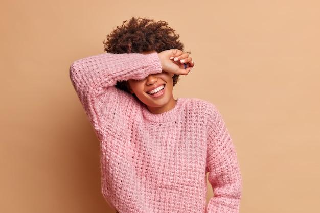 Rozradowana młoda kobieta śmieje się radośnie i uśmiecha się szeroko, ukrywa oczy z ramieniem w dobrym nastroju, słyszy zabawną historię, śmieje się, gdy słyszy anegdotę ubraną w sweter odizolowaną na brązowej ścianie